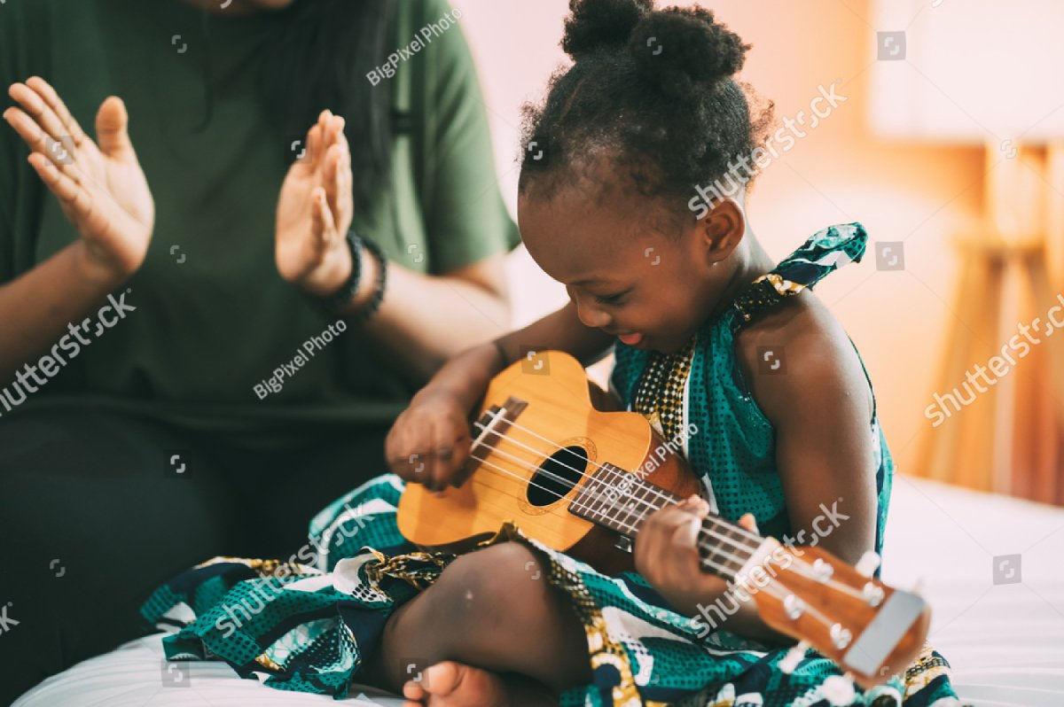 Happy mom clapping while her little daughter singing and playing guitar