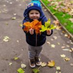 kid standing with leaves in both hands